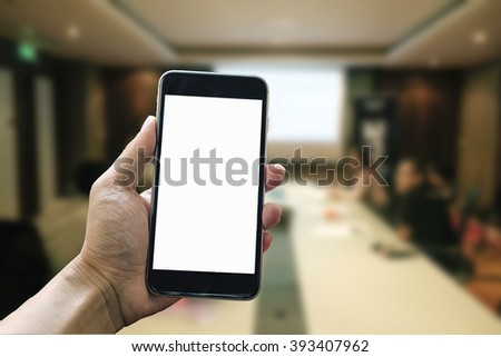 A man hand holding smart phone device in meeting room - stock photo