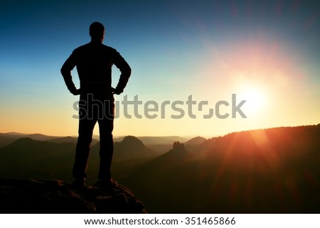 A man has his hands on  hips. Sportsman  silhouette in nature within  daybreak. - stock photo