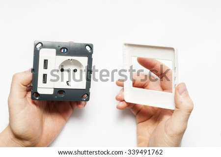 A man hold the socket with two usb charger ports, without decorating pane.