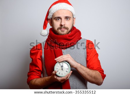 A man holding a alarm clock. Happy Businessman wearing a Santa hat on New Year's corporate parties. Studio photo, isolated - stock photo