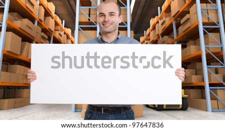 A man holding a blank board in a distribution warehouse, ideal for inserting your own message - stock photo
