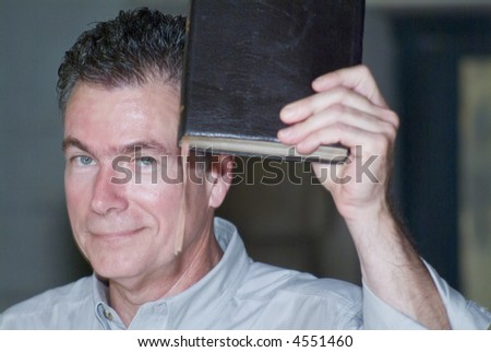 A man holding a book which could be a bible up in the air. - stock photo