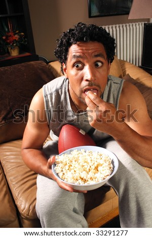 A man holding a football eating popcorn looking very surprised