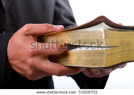 A man holding a large book, like the holy bible