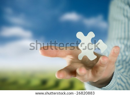 A man holding a puzzle piece. - stock photo