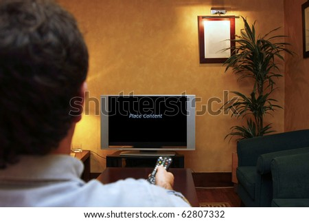 A man holding a remote control while watching TV. Empty space to place content. - stock photo