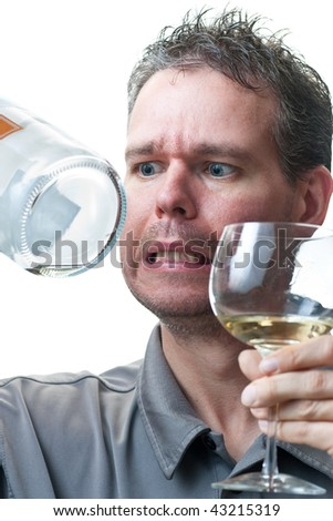 A man holding a wine glass and bottle, with exaggerated concern on his face as he examines the empty bottle, isolated on white.