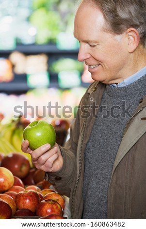 A man holding an apple in grocery store