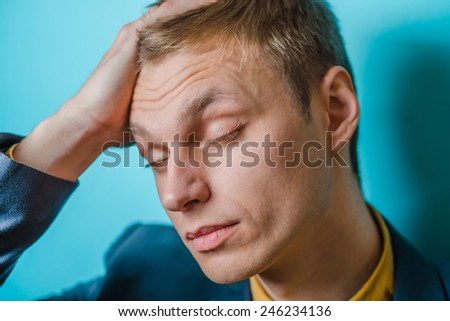 A man holding his head in pain as a result of a headache - stock photo