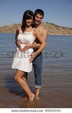 A man holding his woman in the water while making a heart on her belly with his fingers. - stock photo