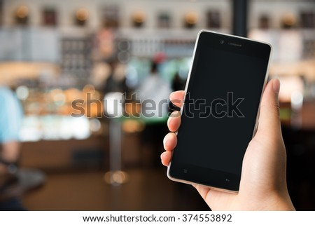 A man holding modern smart phone with blank screen in hand. Closeup shot.
