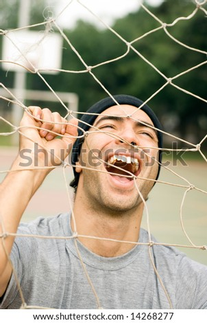 A man holding onto a soccer goal net, smiling and yelling though it. - vertically framed - stock photo