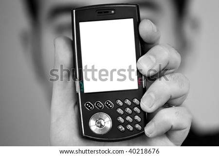 A man holding up a cellular phone.  Clipping path included for the white space on the lcd screen. - stock photo