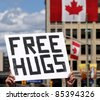 A man holding up a 'Free Hugs' sign on Canada Day in downtown Ottawa, Ontario, Canada. - stock photo