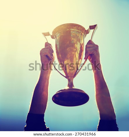 a man holding up a gold trophy cup as a winner in a competition toned with a retro vintage instagram filter effect app or action (backlit with the sun) - stock photo