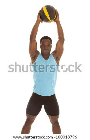 A man holding up his medicine ball up in the air with a serious expression  on his face - stock photo