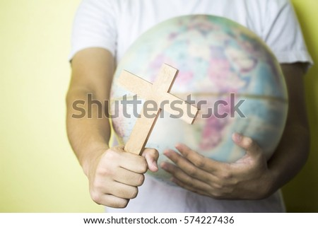 a man holding wooden cross with burred of world globe in other hand over yellow background, christian conceptual image or background
