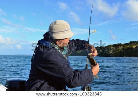 A man holds a fish that he caught during fishing at sea on a fishing boat.