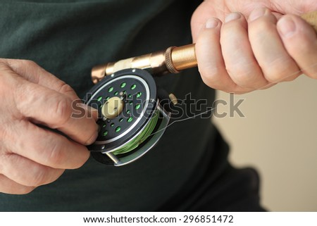 A man holds a fly fishing rod and reel. - stock photo