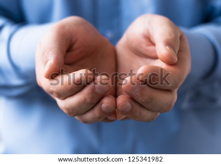 A man holds a handful, hands together, asks - stock photo