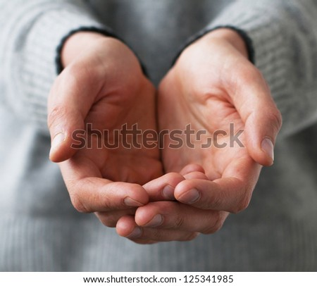A man holds a handful, hands together, asks