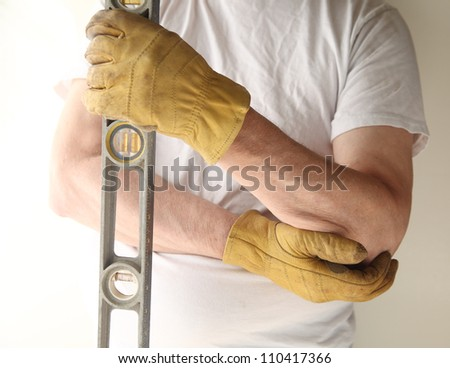 a man holds a level in one hand and tends to his painful elbow with the other - stock photo