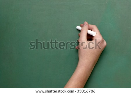 A man holds a piece of chalk, as if ready to write on a chalkboard.