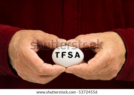 A man holds a white nest egg with TFSA (Tax Free Savings Account, popular in Canada) written on it. - stock photo