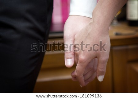 A man holds a woman's hand
