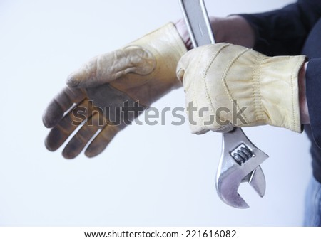 A man holds a wrench while putting on his work gloves. - stock photo