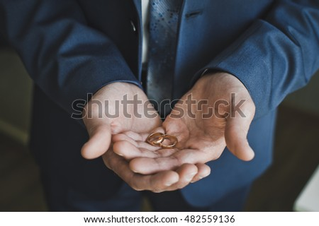 A man holds in his hands a wedding ring.