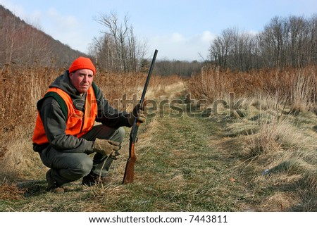 A man hunting in field with gun - stock photo