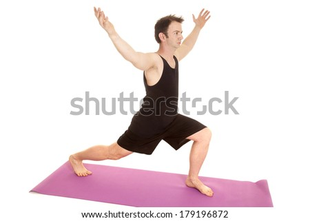 A man in a black tank top doing some yoga. - stock photo