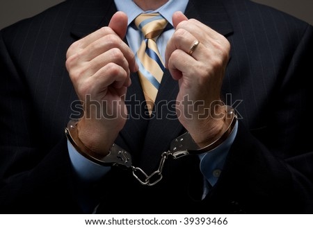 A man in a blue business suit holding hands in handcuffs in front of his chest- white collar or corporate crime - stock photo