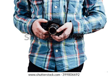A man in a blue plaid shirt holding camera in the hands.  Closeup. White isolated background.