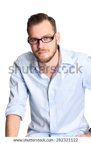 A man in a blue shirt and glasses sitting down in a studio setting. Feeling great with a big smile. White background. - stock photo