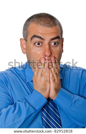 A man in a blue shirt tie poses anxiously covering his mouth with his hands isolated on white background - stock photo