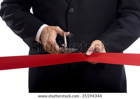 A man in a business suit cutting a red silk ribbon with shiny scissors, grand opening or beginning concept - stock photo