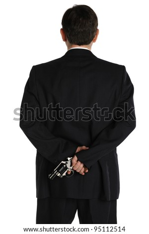 A man in a business suit hides a pistol behind his back - stock photo