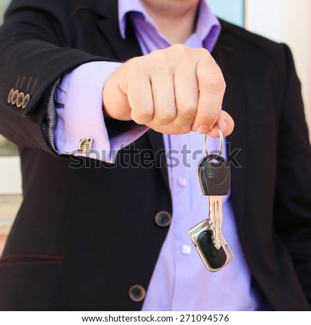 A man in a business suit holding key with remote control  - stock photo