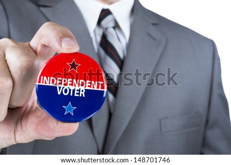 A man in a business suit holds out a political independent voter pin during elections. - stock photo
