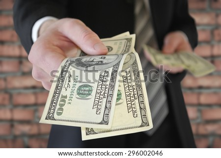 A man in a business suit offers money - stock photo