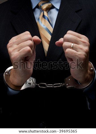 A man in a business suit with handcuffs - stock photo