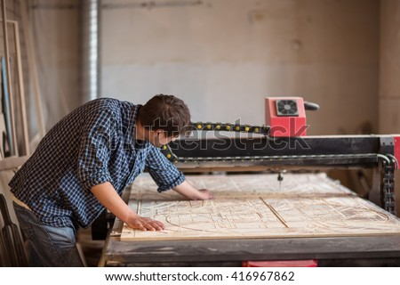 a man in a carpenter's shop with a large CNC milling machines, lifestyle, hobbies, their production, small business - stock photo