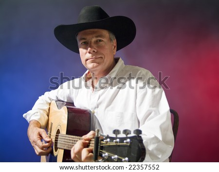 A man in a cowboy hat playing a guitar, colorful, smokey background.