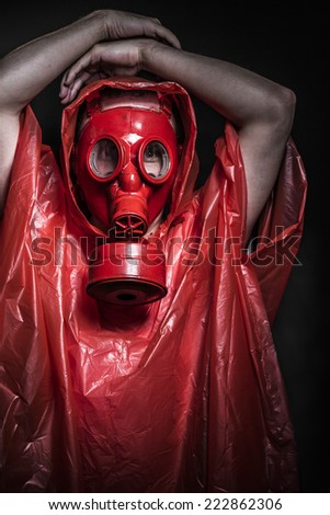 A man in a gas mask over  the smoke. black background and red colors - stock photo
