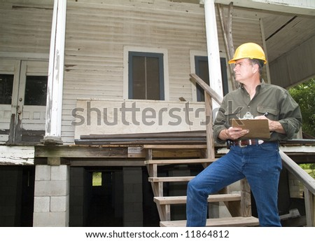 A man in a hard hat, holding a clipboard, standing on the steps of an old rundown house. - stock photo