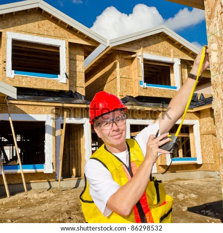 A man in a hard hat standing in front of an house holding a measure tape in his hand. - stock photo