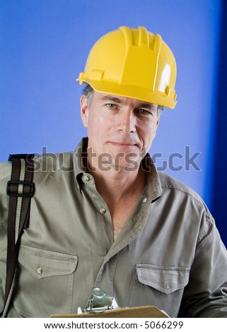 A man in a hard hat with something hanging on his shoulder and a clipboard in his hand. - stock photo