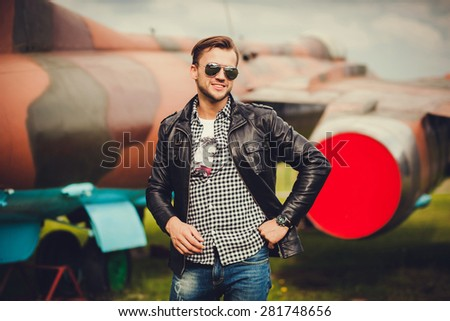 a man in a leather jacket and sunglasses smiling. planes in the background - stock photo